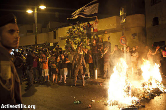 """An Israeli mob setting garbage on fire and singing """"The people wants the Africans to be burned"""" after a protest against African refugees and asylum seekers in Tel Aviv's Hatikva neighborhood on May 23, 2012. (Photo: Activestills)"""