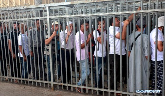 Palestinians wait to cross Qalandia checkpoint on their way to attend Ramadan Friday prayers in Jerusalem on Aug. 3, 2012. (Photo: Xinhua/Fadi Arouri)