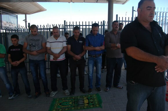 Palestinians pray in protest of the a-Zeitim checkpoint that bisects East Jerusalem neighborhoods. (Photo: Allison Deger)