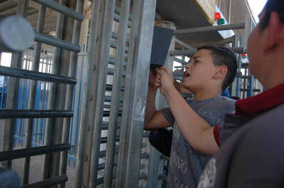 Palestinian Jerusalem ID holders use call box at a-Zeitim checkpoint to ask the Israeli army to open to crossing. (Photo: Allison Deger)