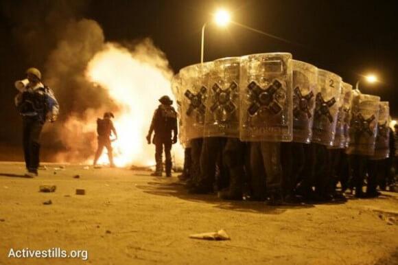 Police push back activists towards Hura. Photo: Activestills.org.
