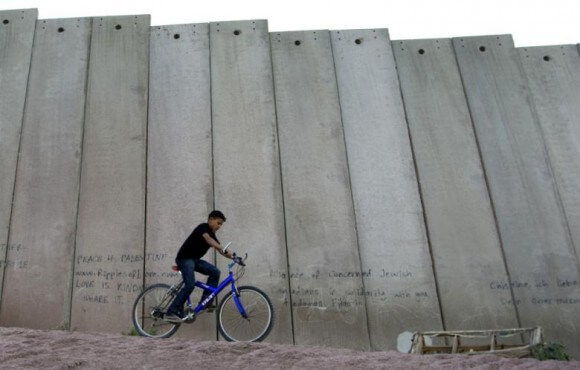 """A Palestinian youth rides his bicycle next to Israel's """"apartheid wall"""" on the outskirts of Jerusalem. (Photo: Ahmad Gharabli/AFP/Al Akhbar English)"""