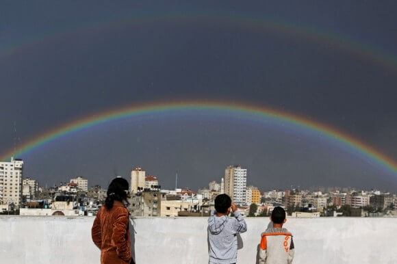 Palestinian children look at a double rainbow after heavy rain flooded Gaza on Dec. 12, 2013. (photo: Hatem Moussa/AP)