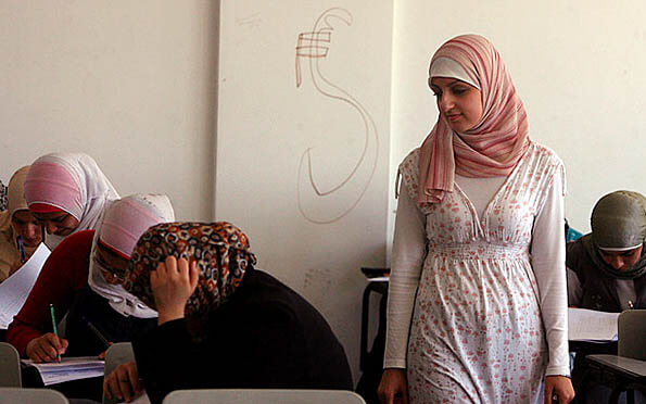 23-year-old software engineering instructor Hadeel Abukwaik (standing) initially lost her Fulbright grant because Israel refused her exit from Gaza.