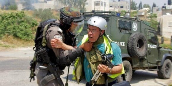 Bilal Tamimi being attacked by an Israeli soldier during demonstration in Nabi Saleh, May 2013. Photo by Tamimi Press, used in Amnesty Int'l report