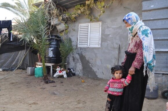 Amna standing with her two-year old daughter in the yard of her house.