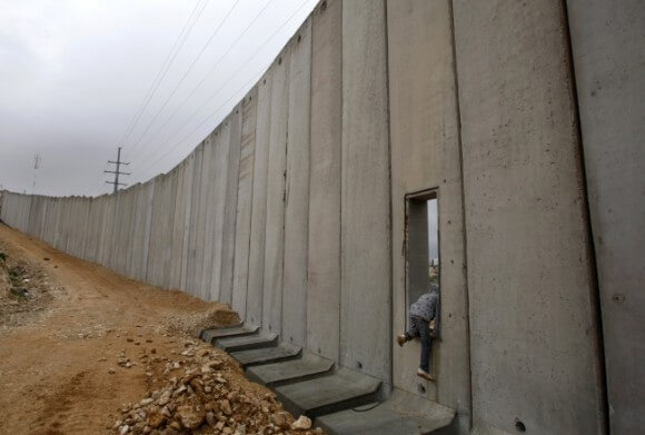 Palestinian boy climbs through an opening in Israel's separation barrier in Shuafat near Jerusalem.  February, 2009. (Photo: REUTERS/Baz Ratner)