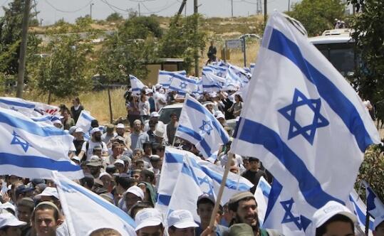 Settlers hold Israeli flags as they march near the Ulpana neighbourhood of the Beit El settlement. (Photo: REUTERS/Ronen Zvulun)