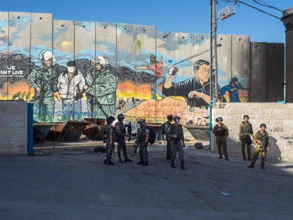 Israeli Soldiers and Border Police stand in front of the Wall in Aida Camp. (Photo: Adam Wolf)