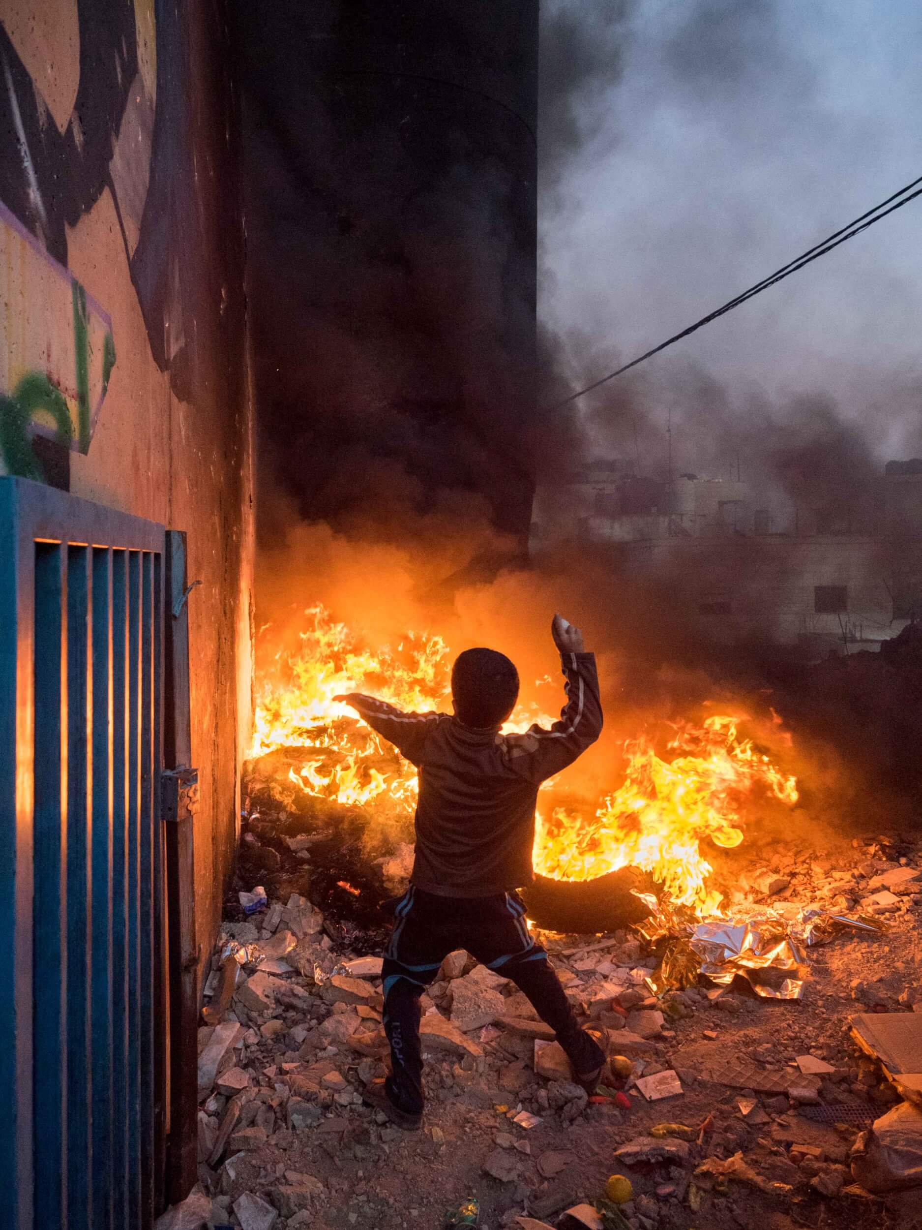 A boy throws a rock at the burning tower. (Photo: Dan Cohen)