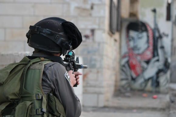 Border Policeman aims his rifle down an alleyway. (Photo: Mohammed Al-Azza)