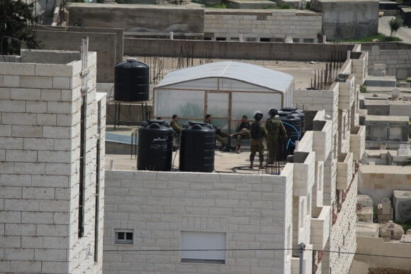 Israeli soldiers relax atop an occupied home. (Photo: Mohammed Al-Azza)