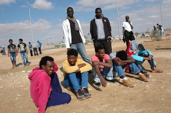 "African asylum seekers enjoying the benefits of forced relocation to the ""open facility"" of Holot, sitting in the desert sun. (Photo: Allison Deger)"
