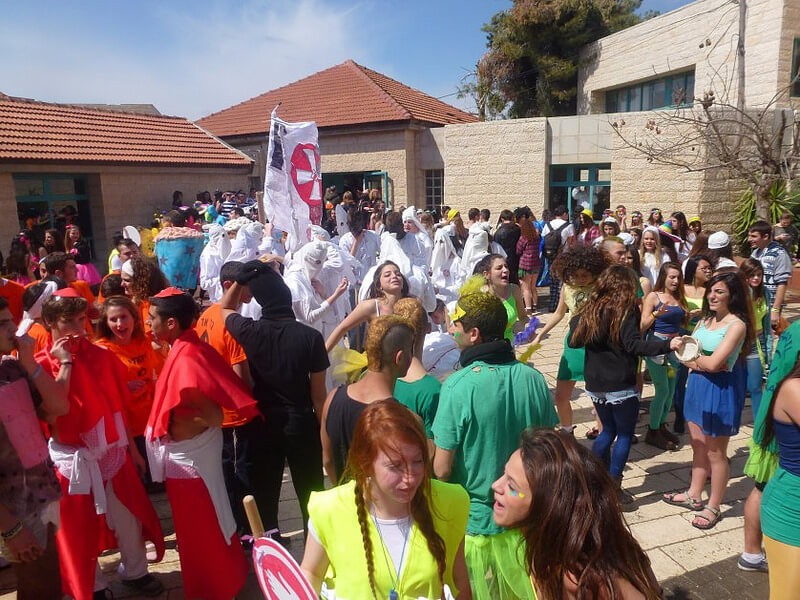 Purim carnival, students in KKK robes and black face in the background. (Photo: Harel High School/Flickr)