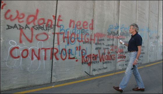 Roger Waters spray paints Israel's separation barrier. (Imaga via WagingNonViolence.org)