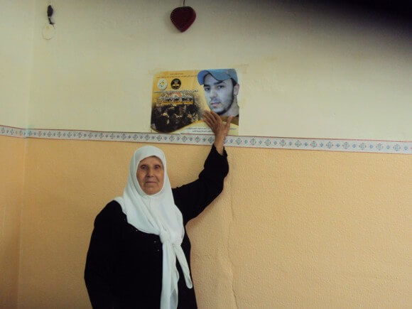 Majd Lahlouh's grandmother points to a poster of Majd. (Photo: Alex Kane)