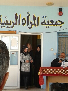 """Mayor Haj Sami welcomes the guests.  In Arabic above the door it reads, """"Rural Women's Society"""""""