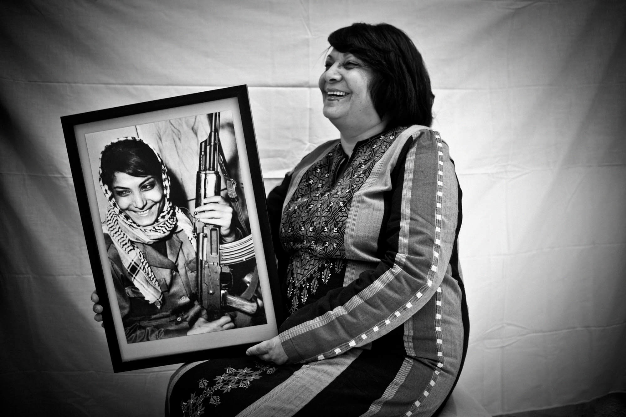 Leila Khaled holding a photo of her younger self in 2009 (Photo: Tanya Habjouqa)