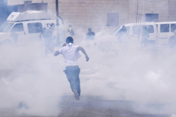Palestinian boy running away from the teargas in Ofer – 16th of May 2014. (Photo: Julie Pronier)
