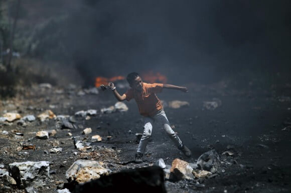 Palestinian boy throwing stones against Israeli soldiers during clashes near Nablus, Palestine May 2, 2014.