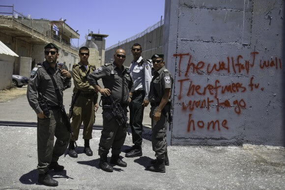 Israeli soldiers stand beside a recently painted slogan after opening the military gate  near Rachel's Tomb in response to Palestinian activists from Aida Refugee Camp May 24th,  2014. (Photo: Kelly Lynn)