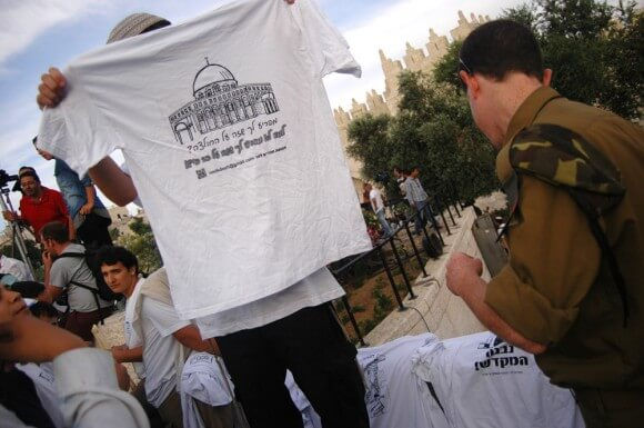 Kahanist youth holds up a tee-shirt calling for the destruction of the Dome of the Rock. (Photo: Allison Deger)
