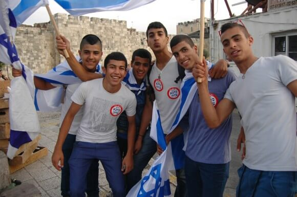 """Israeli teens wear """"Kahane was right"""" stickers over their school tee-shirts at the Jerusalem Day parade. (Photo: Allison Deger)"""