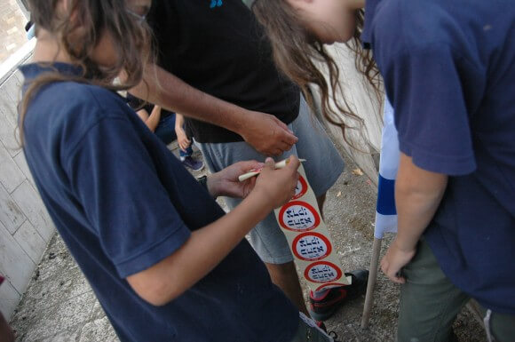 """Youths bring a reel of """"Kahane was right"""" stickers to their father during the Jerusalem Day march. (Photo: Allison Deger)"""