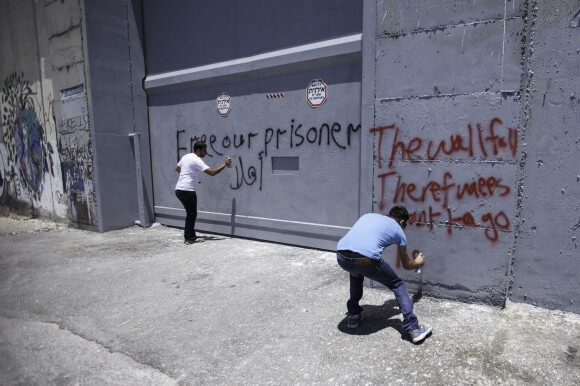 Activists from Aida Refugee Camp paint slogans on a newly painted portion of the  Apartheid Wall and military gate near Rachel's Tomb in Bethlehem on May 24th, 2014. (Photo: Kelly Lynn)