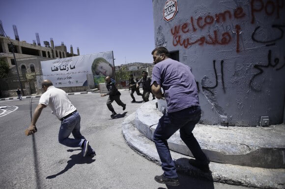 A Palestinian activist runs after painting the sniper tower near Rachel's Tomb in  Bethlehem on May 24th, 2014, as Israeli soldiers attempt to detain him. (Photo: Kelly Lynn)