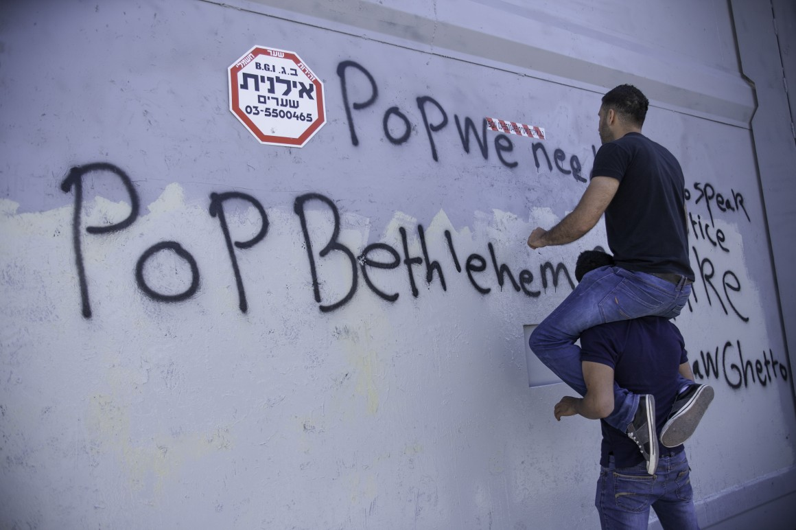 "Mohammed Abu Srour, 23, writes slogans on the military gate which was painted over twice in preparation for Pope Francis's visit May 25th, 2014. The completed slogans read, ""Pope, we need some1 to speak about justice,"" and ""Pope, Bethlehem look like Warsaw Ghetto."" (Photo: Kelly Lynn)"
