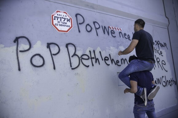 """Mohammed Abu Srour, 23, writes slogans on the military gate which was painted over twice in preparation for Pope Francis's visit May 25th, 2014. The completed slogans read, """"Pope, we need some1 to speak about justice,"""" and """"Pope, Bethlehem look like Warsaw Ghetto."""" (Photo: Kelly Lynn)"""
