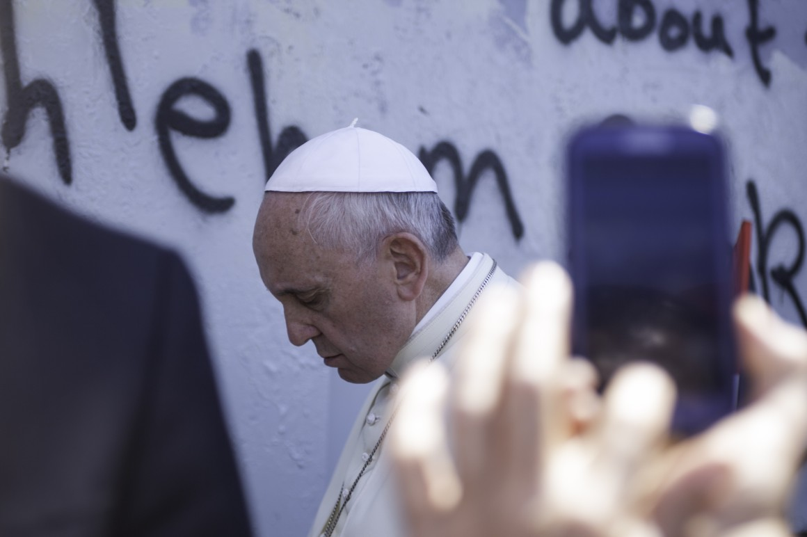 Pope Francis backs up slowly with his head bowed after praying at the military gate in the Israeli built Apartheid Wall on May 25th, 2014. (Photo: Kelly Lynn)