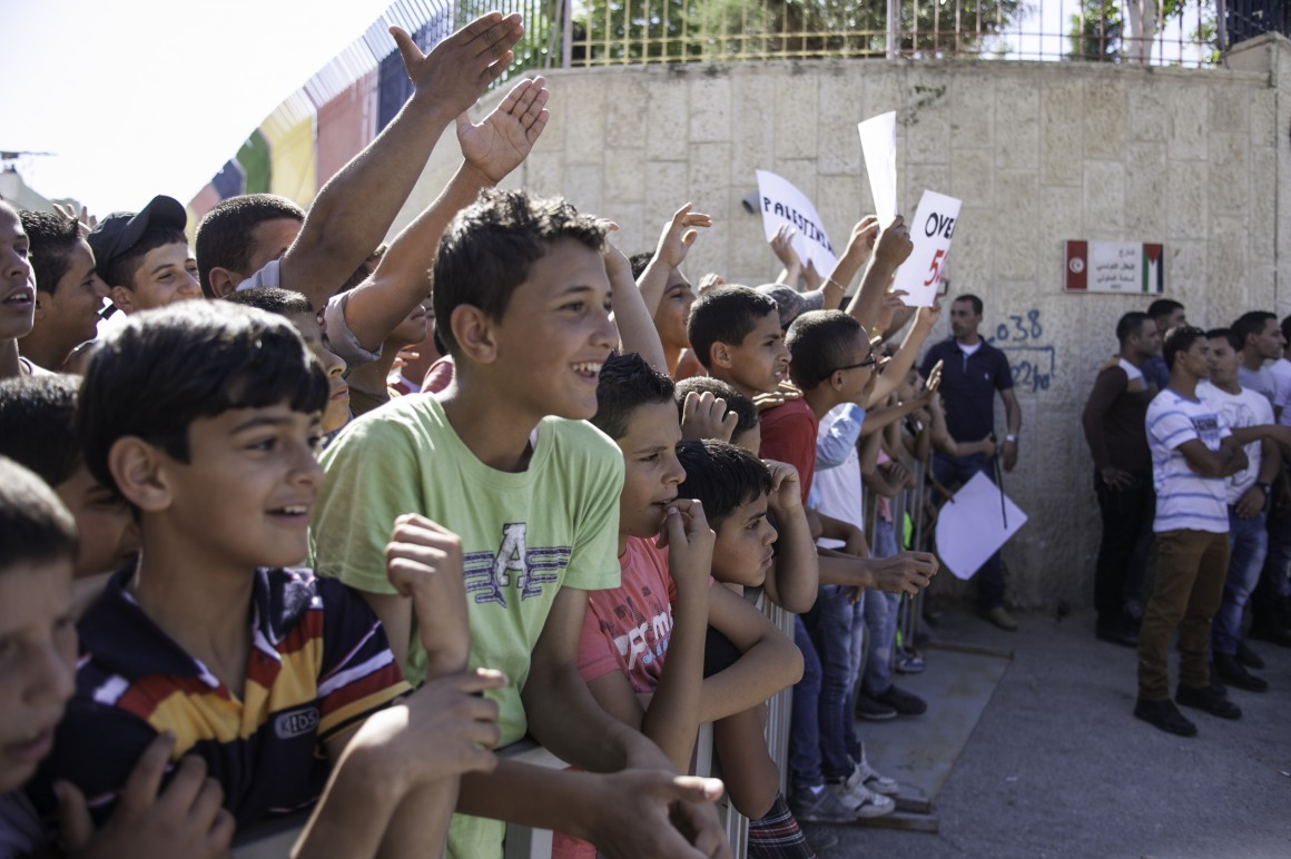 Children from Dheisheh Refugee Camp wave as Pope Francis passes in a caravan on his way to meet with young refugees from Bethlehem's three camps, Dheisheh, Aida and Azza, on May 25th, 2014. (Photo: Kelly Lynn)
