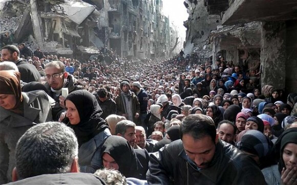 Palestinian residents of the besieged Yarmouk refugee camp line up to receive food supplies, March, 2014. (Photo: AP)