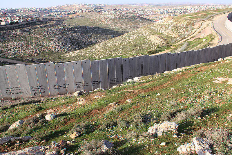 The Separation Wall cuts through the West Bank landscape. (Photo: WIkipedia)