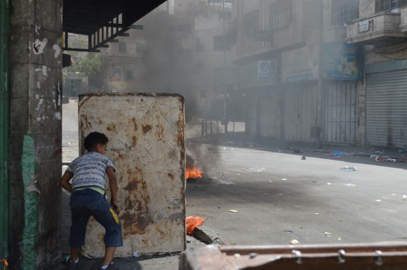 A young boy pushes a makeshift scrap metal barrier for protection from the IDF. (Photo: Sheren Khalel)