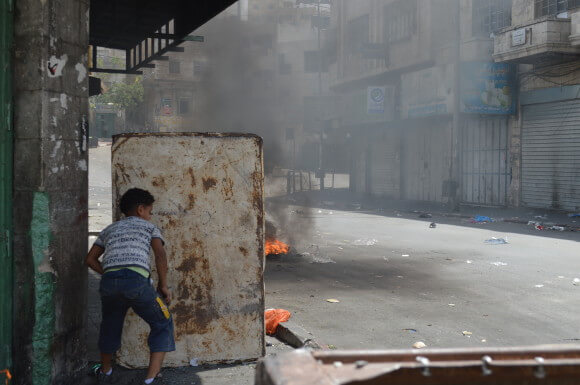 A young boy pushes a makeshift scrap metal barrier for protection from the IDF in Hebron, June 22, 2014. (Photo: Sheren Khalel)