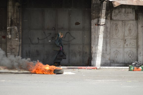 A woman walks by a burning tire in the city center, trying to avoid the clashes. (Photo: Sheren Khalel)