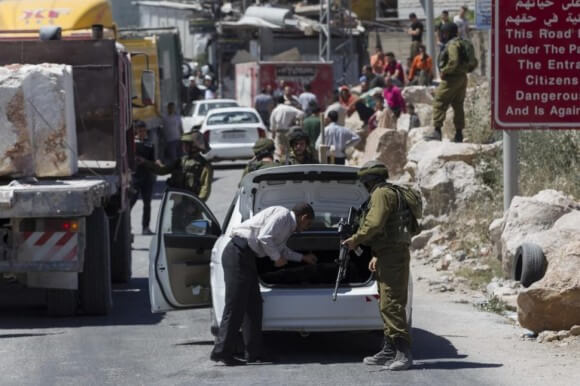 Israeli soldier searches a Palestinian vehicle at a checkpoint near Hebron on Sunday, three days after the teenagers disappeared from the West Bank. (Photo: Reuters)