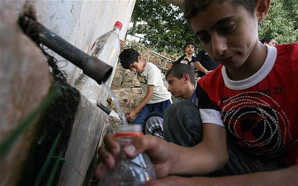 Palestinian children fill jars and bottles from a pipe transporting water from a village spring in the village of Dar al-Hatab near the West Bank town of Nablus (Photo: Getty Images)