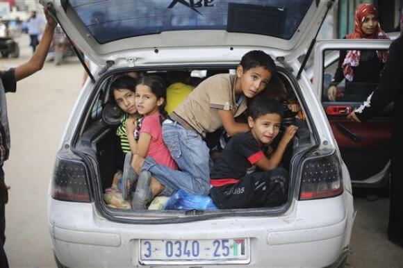 Palestinian children hide in a car trunk as they flee their family homes following heavy Israeli shelling during an Israeli ground offensive east of Khan Younis, in the southern Gaza Strip July 23, 2014. (Photo: Reuters)