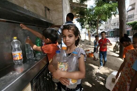 Palestinian children fill their bottles with drinking water at a groundwater desalination unit in Rafah, south Gaza Strip, on 13 July. Photo: UNICEF/El Baba