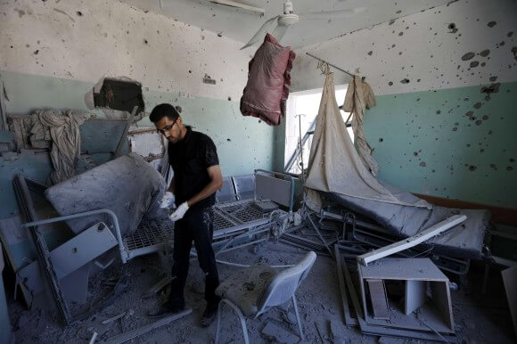 A Palestinian employee inspects damages at the Al-Aqsa Martyrs hospital in Deir al-Balah, in the central Gaza Strip, after the building was shelled by the Israeli army on July 21, 2014, killing five people and wounding at least 70. (Photo: Mohammed Abed/AFP)