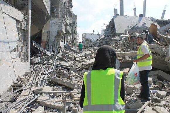Internationals follow a Palestinian youth who is seeking his family in Shuja'iyeh, photo by Joe Catron
