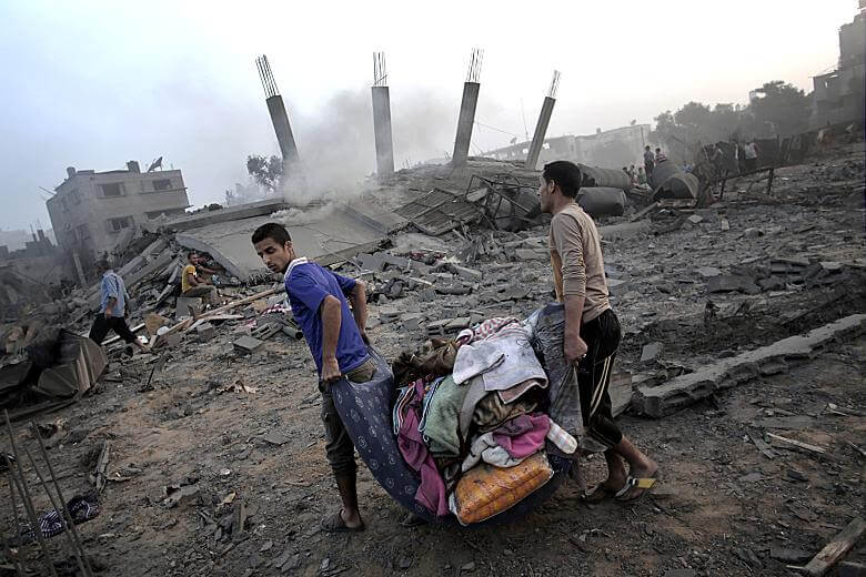 Palestinians collect their belongings from damaged houses in Gaza City. (Photo: Mahmud Hams / AFP / Getty Images)