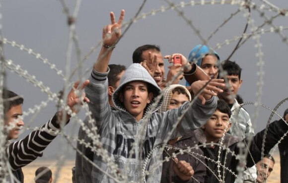 Palestinian youths gesture during a demonstration next to the security fence standing on the Gaza border, east of Khan Yunis, in the Gaza Strip, on November 23 2012. (Photo: AFP - Said Khatib)