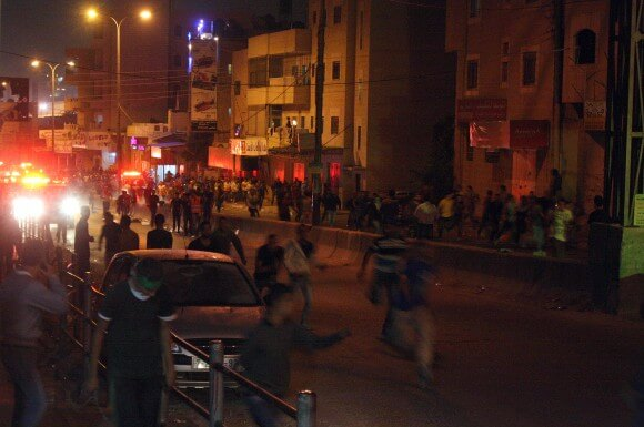 Palestinian protesters fleeing from Israeli gunfire after reaching the checkpoint. (Photo: Martin Gajsek)