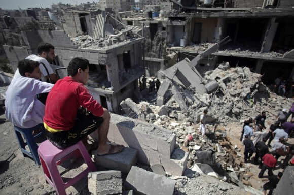 Palestinians search in the rubble of a destroyed house where eight members of the Al Haj family were killed in a strike early morning in Khan Younis refugee camp, southern Gaza Strip on Thursday, July 10, 2014.  (Photo: AP/Khalil Hamra)