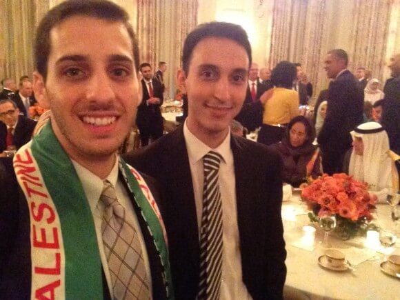 Tarik Takkesh, left, standing with an acquaintance with President Obama in the background.
